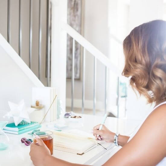 woman writing at desk - how to be a productive mom - choose 1 or 2 major activities for the day