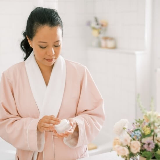 woman doing skincare - productivity tips for moms - make time for self care