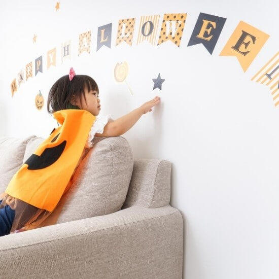 child playing in room of decor as a halloween social media ideas post