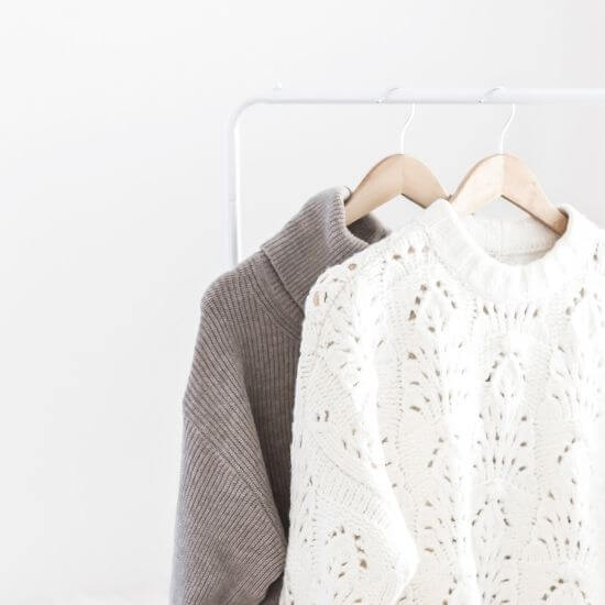 christmas blog post ideas - fashion, grey and white sweaters hanging on clothing rack - fashion blog post ideas for christmas