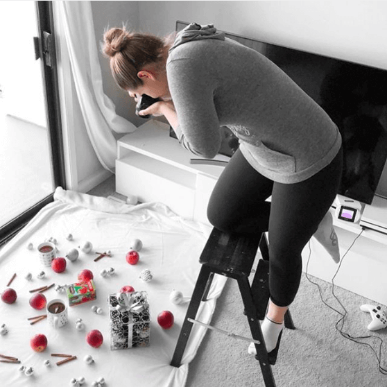 image of nikki standing on a stool taking top down photos for a christmas campaign on instagram