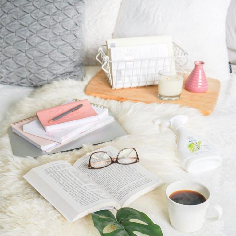 shows a comfortable blogging setup on grey and white bedding