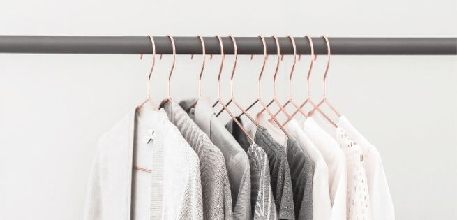 things to stop buying - clothes! shows clothing hanging on rack