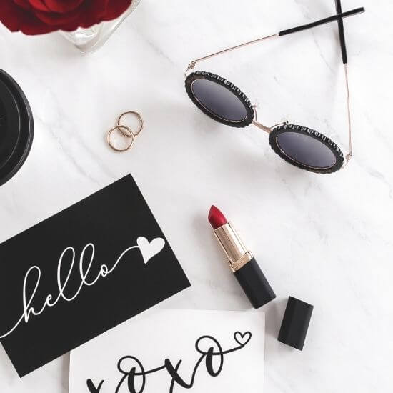 valentine's day ideas - top down of lipstick, sunglasses, and romantic notes