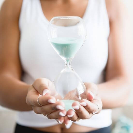 woman holding an hour glass to represent questions to ask yourself - where do you want to spend your time?