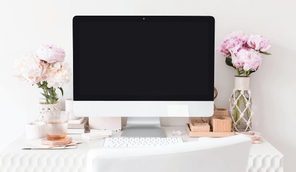 imac computer on a white desk with white office chair and floral decor