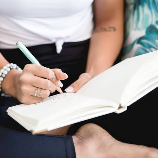 woman writing in a journal - self improvement ideas for bloggers