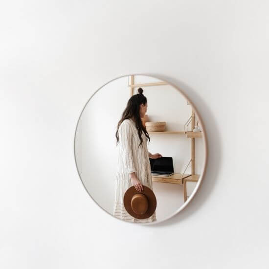 woman's reflection in mirror - questions to ask yourself: how do you want to come across?