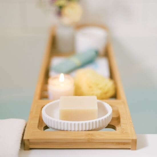 variety of bath products in a wooden tray - self care ideas for moms