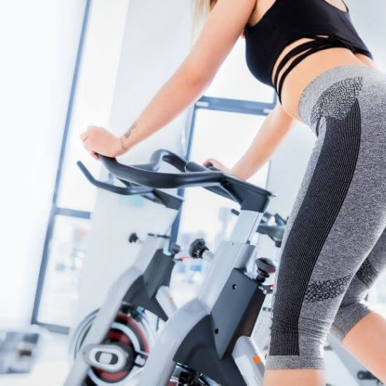 woman doing a spin cycling workout like peloton - self care ideas for moms