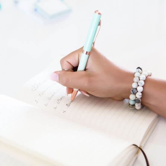 hand holding a pen writing to do list - self care ideas for moms