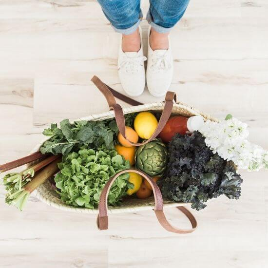 top down photo of a women's sneakers and reusable grocery bag full of healthy veggies - wellness blog ideas
