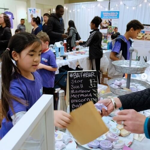 a child sells bath bombs on build a biz kids market day