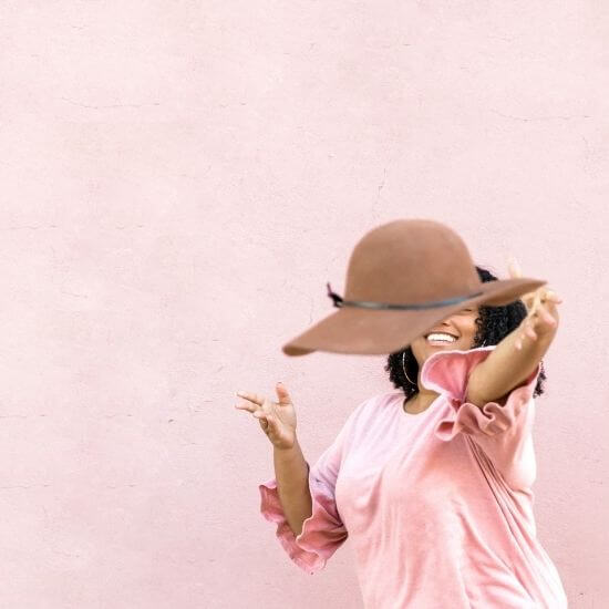 cute first instagram post ideas -fashion blogger throwing a hat