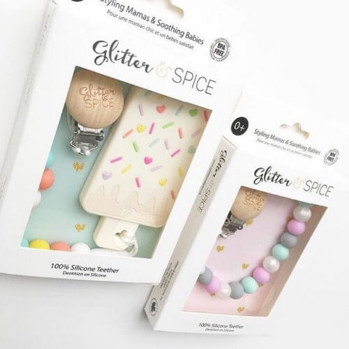two packaged teethers from glitter and spice featuring wooden clips and silicone bodies
