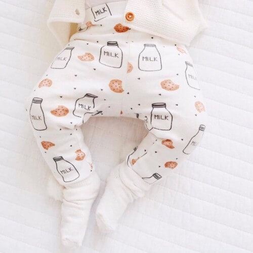 top down photo of a baby wearing kewe clothing cookies and milk pants