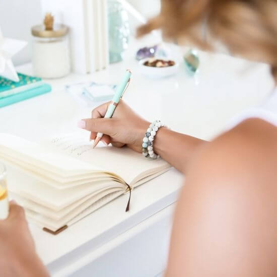 top down photo of a woman writing - best jobs for stay at home moms with no experience include blogging