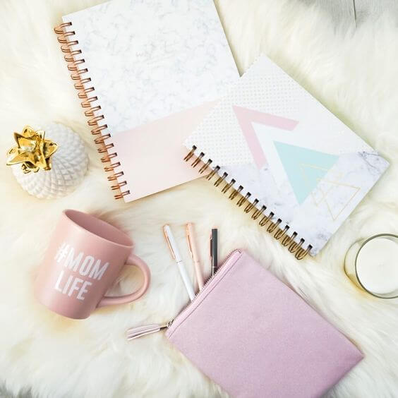 flat lay photo of stationary including a mug, books, and pens