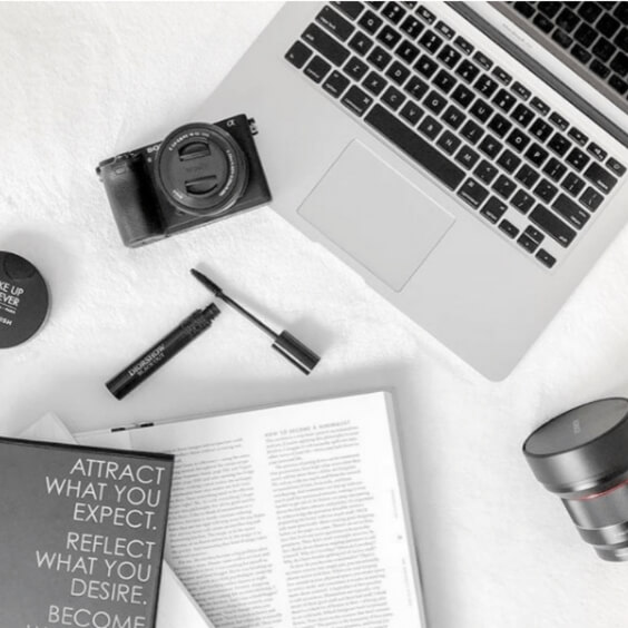 tech styled flat lay photo for instagram featuring computer, camera, books, makeup, and lens