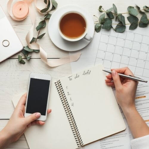 how to write a to do list tips - top down of a woman writing a to do list with phone and tea