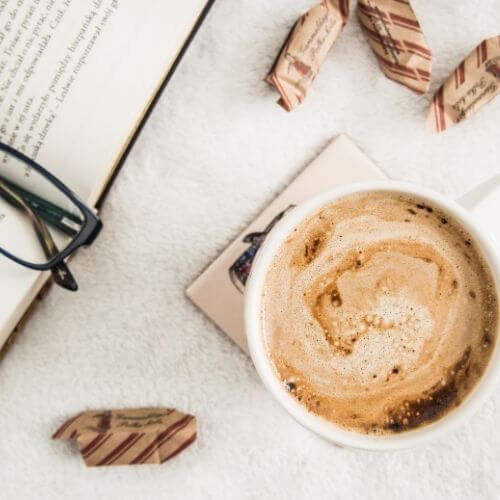 how to stay focused - top down of coffee, glasses, and a book