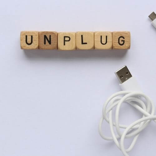 how to stay focused and boost concentration tips - top down photo of usb cable and scrabble letters that spell unplug