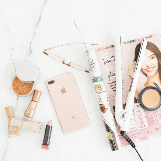 top down photo of beauty products including foundation, lipstick, straight iron, and power. Pink iphone and magazine lay underneath