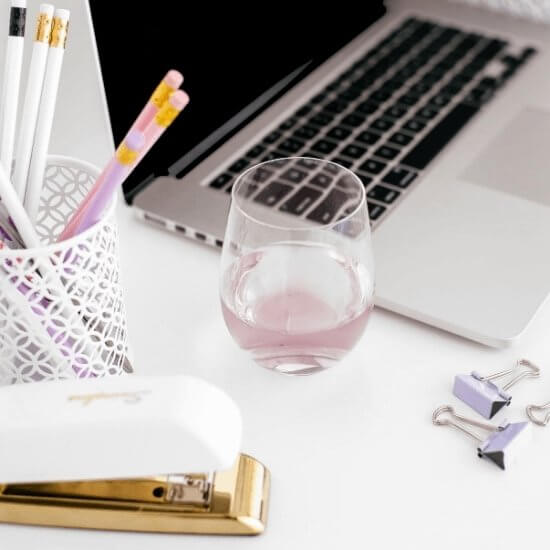start a blog on instagram tips - side view of a computer, stationary, and berry drink on top of a white workspace