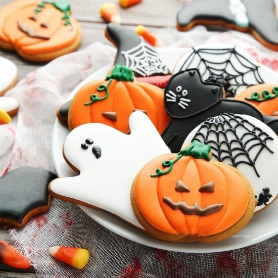 halloween cookies on a white plate - ghost, pumpkins, and spider shapes