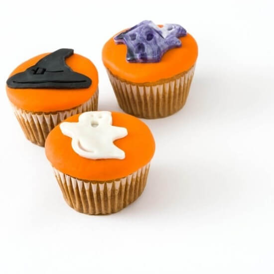 orange halloween cupcakes decorated with a ghost, witch's hat, and monster