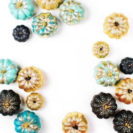 top down image of glitter painted pumpkins in blue, gold, and black