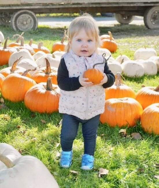 nikki's daughter holding a small pumpkin and walking towards camera
