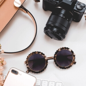 top down photo of a camera and feminine accessories