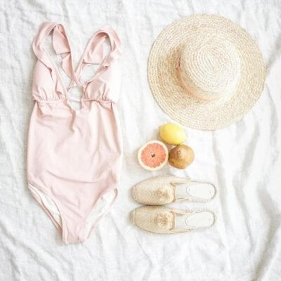summer vacation blog post - flat lay of one piece swimsuit, hat, shoes, and fruit