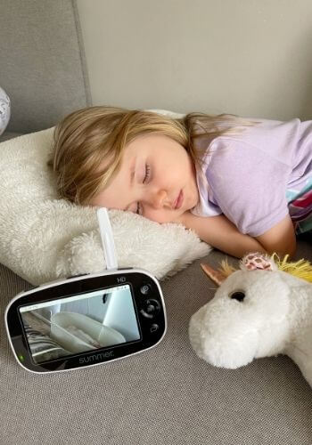 baby sleeping in snoo on monitor while toddler sleeps on couch